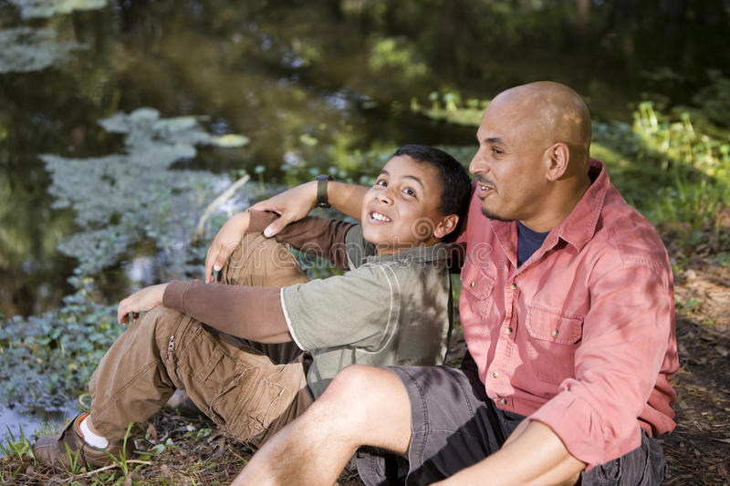 Portrait Hispanic father and son outdoors by pond royalty free stock photo