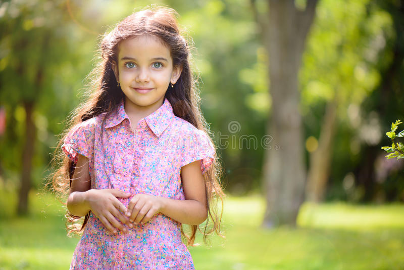 Portrait of hispanic girl in sunny park royalty free stock photography