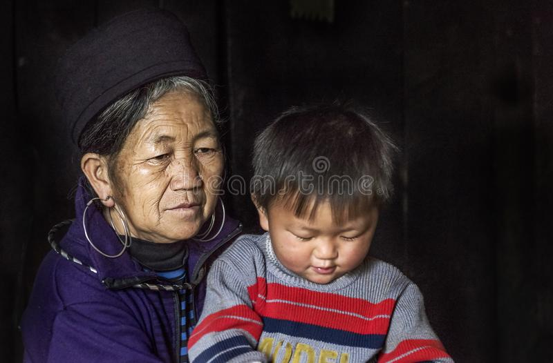 Portrait of Hmong tribe grandmother and her grandson in her traditional house in Sapa, Vietnam royalty free stock images