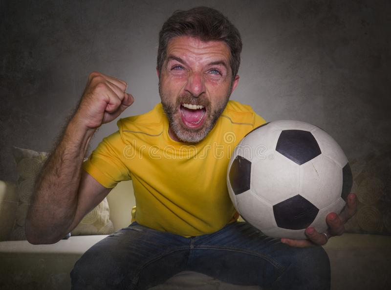 Young happy and excited man watching European football game on TV celebrating goal on couch screaming spastic gesturing crazy royalty free stock photography