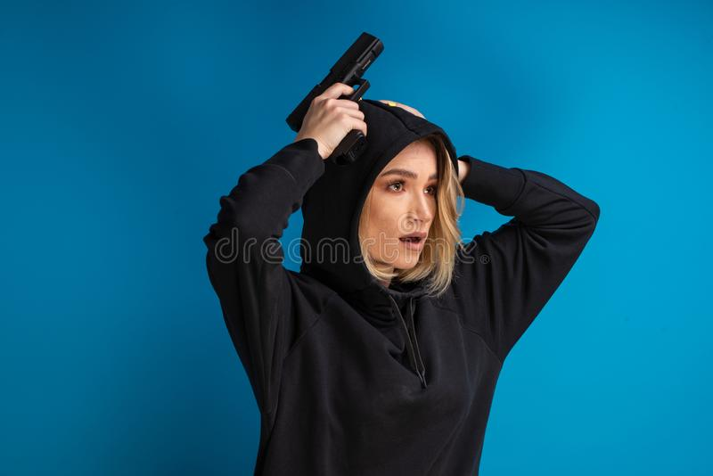 Portrait of hooded girl looking shocked while holding her hands with gun up on the head royalty free stock photography