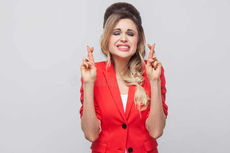 Portrait of hopeful beautiful business lady with hairstyle and makeup in red fancy blazer, standing, clenching teeth, closed eyes. And crossed fingers. indoor stock photography