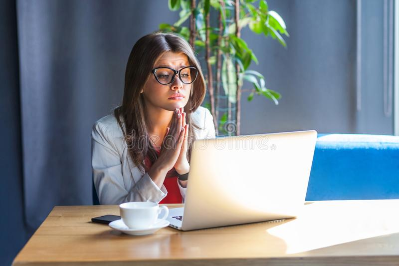 Portrait of hopeful beautiful stylish brunette young woman in glasses sitting, looking at her laptop monitor with worry face and. Begging or pleading. indoor stock images