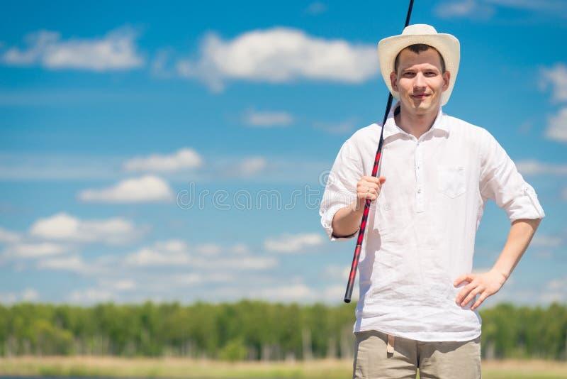 Portrait horizontal d'un pêcheur avec une canne à pêche en nature image stock