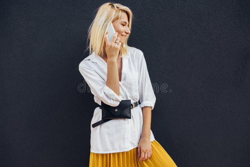 Portrait horizontal de la femme blonde d'affaires souriant et se tenant contre le mur du bâtiment gris tout en parlant sur le tél image stock
