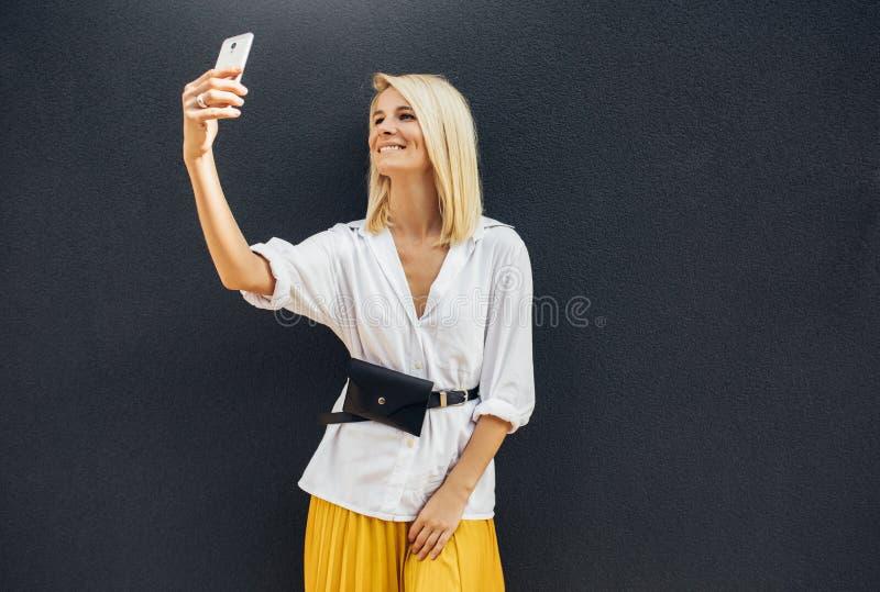 Portrait horizontal de la position heureuse de femme à côté du mur gris tout en parlant l'autoportrait au téléphone intelligent L image libre de droits