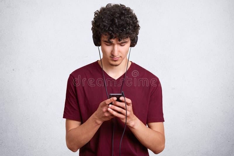 Portrait horizontal de transmission de messages et de bloguer de jeune homme sur le téléphone portable tandis que musique de écou photos stock