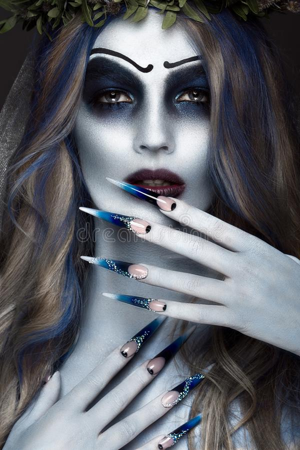 Portrait of a horrible scary Corpse Bride in wreath with dead flowers, halloween makeup and long manicure.Design of. Nails.Photo taken in studio royalty free stock image