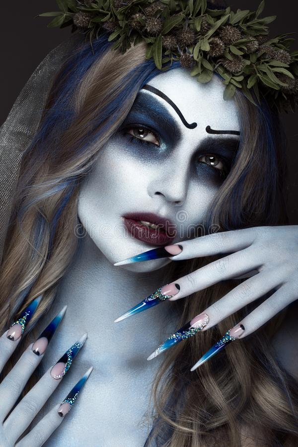 Portrait of a horrible scary Corpse Bride in wreath with dead flowers, halloween makeup and long manicure.Design of. Nails.Photo taken in studio stock image