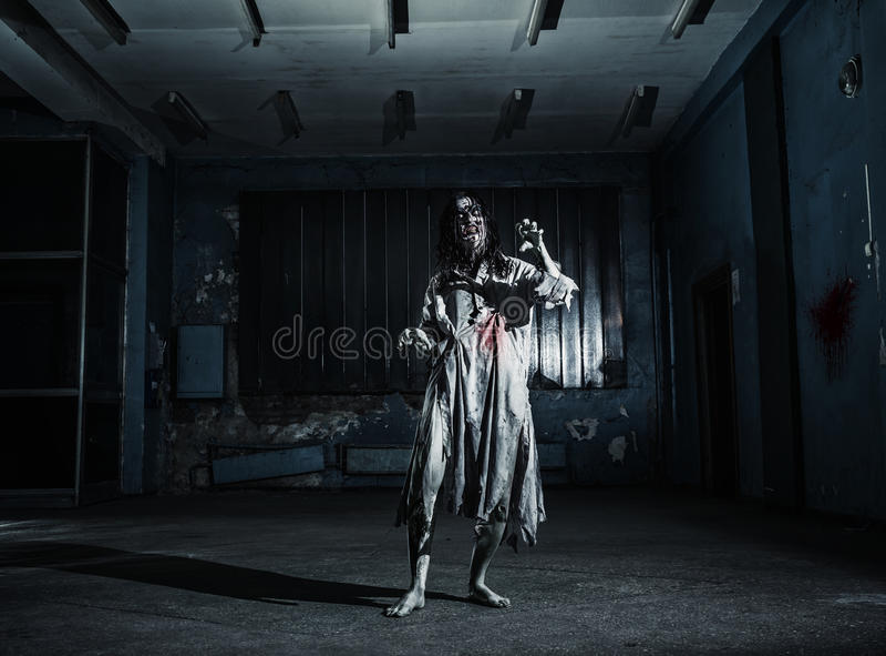 Portrait of the horror zombie woman. Halloween. Portrait of the horror zombie woman in the scary basement. Halloween royalty free stock photo