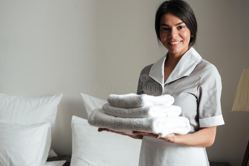 Portrait of a hotel maid holding fresh clean folded towels. Portrait of a smiling hotel maid holding fresh clean folded towels for the room royalty free stock image