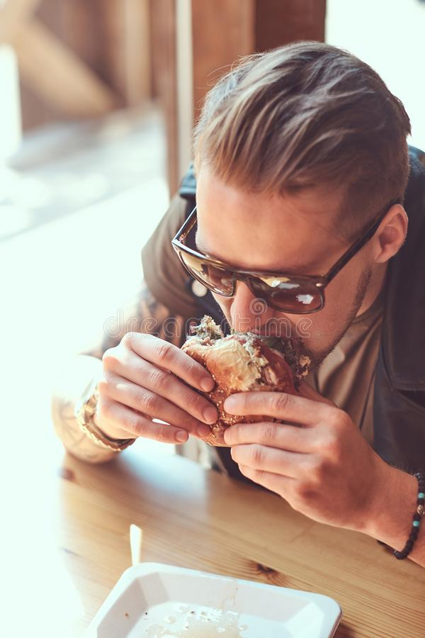 Portrait of a hungry hipster guy with a stylish haircut and beard sits at a table, decided to dine at a roadside cafe royalty free stock photography