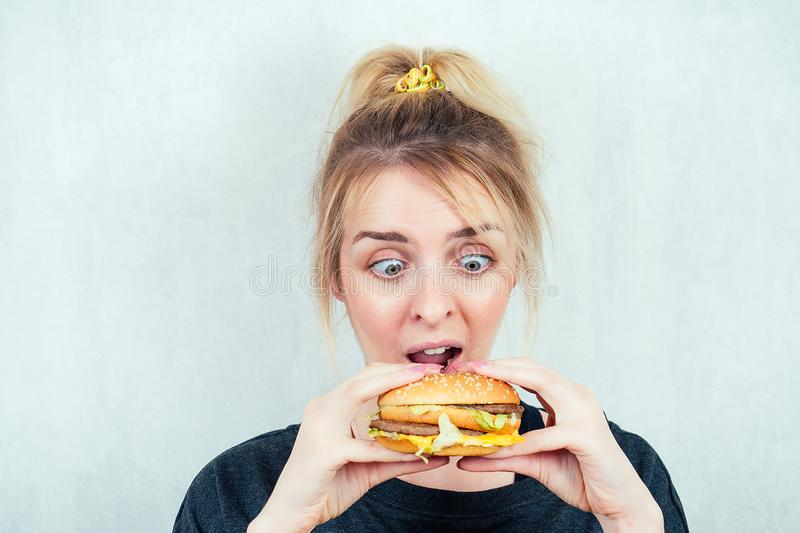 Portrait of a hungry, young and beautiful blonde woman holding a burger cheeseburger in a black T-shirt. concept of diet stock images