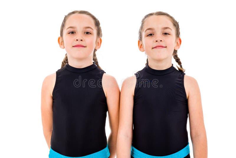 Portrait of identical twin girls dressed in rhythmic gymnastics dress royalty free stock image