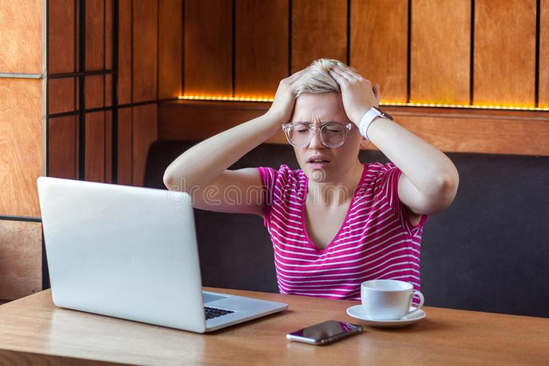 Portrait of illness young adult woman with short blonde hair in pink t-shirt and eyeglasses sitting in cafe and holding head with royalty free stock photos