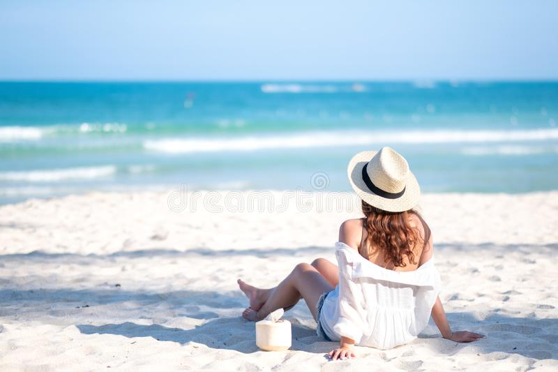 A beautiful asian woman enjoy sitting and drinking coconut juice on the beach stock image