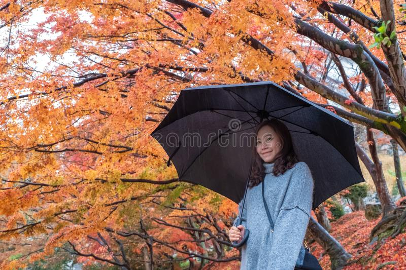 Beautiful asian woman standing in the rain with red and orange tree leaves in autumn background stock photography