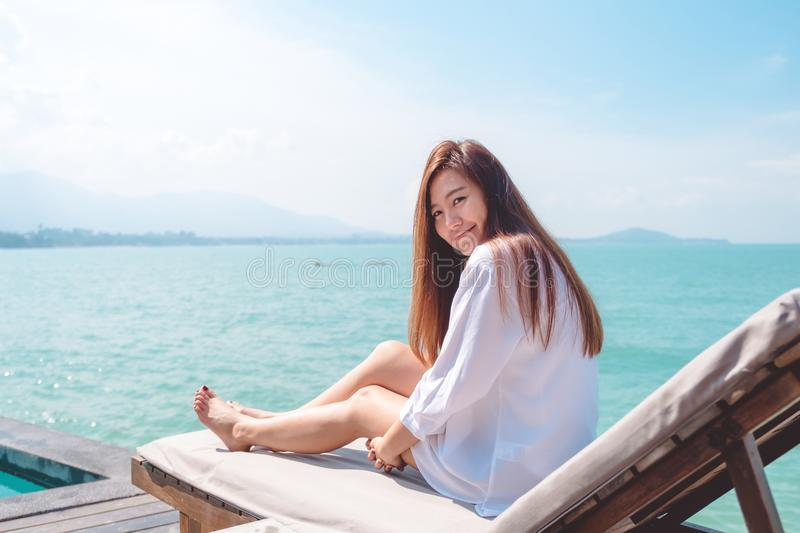 Portrait image of a happy beautiful asian woman on white dress sitting on sun bed by the sea. With blue sky background royalty free stock images