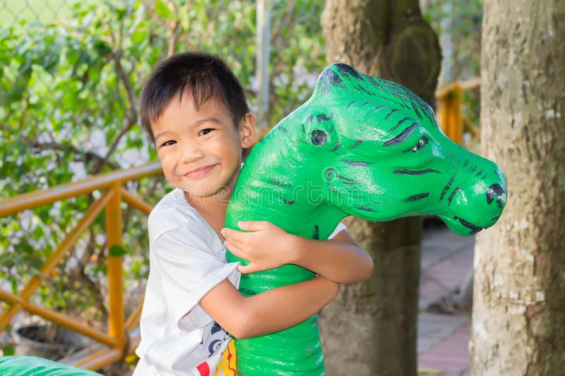 Portrait image of kid 5 years old. Happy Asian child boy playing with dinosaur toy at the playground. stock photography