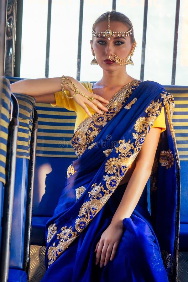 Portrait indian beautiful Caucasian woman in traditional blue dress.hindu model with golden kundan jewelry set bindi royalty free stock image