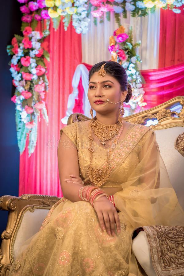 August 2019, Kolkata, India: Portrait of an Indian bride standing with glamorous outfit and jewellery with makeup in a banquet royalty free stock photography