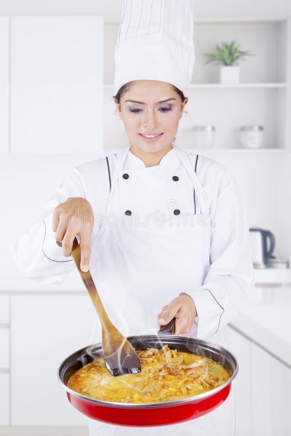 Indian female chef cooking tripe soup in kitchen. Portrait of Indian female chef cooking tripe soup while standing in the kitchen stock images