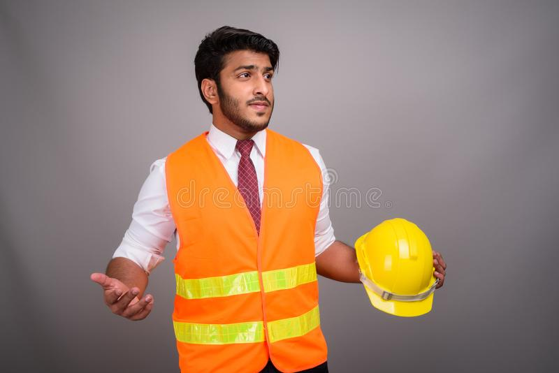 Portrait of Indian man construction worker businessman. Studio shot of young handsome Indian man construction worker against gray background royalty free stock photos