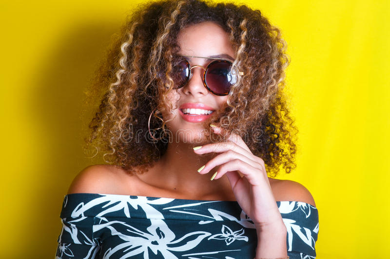 Portrait indoors of a young afro american woman in sunglasses. Yellow background. Lifestyle. Casual clothing. Portrait indoors of a young afro american woman in royalty free stock photography