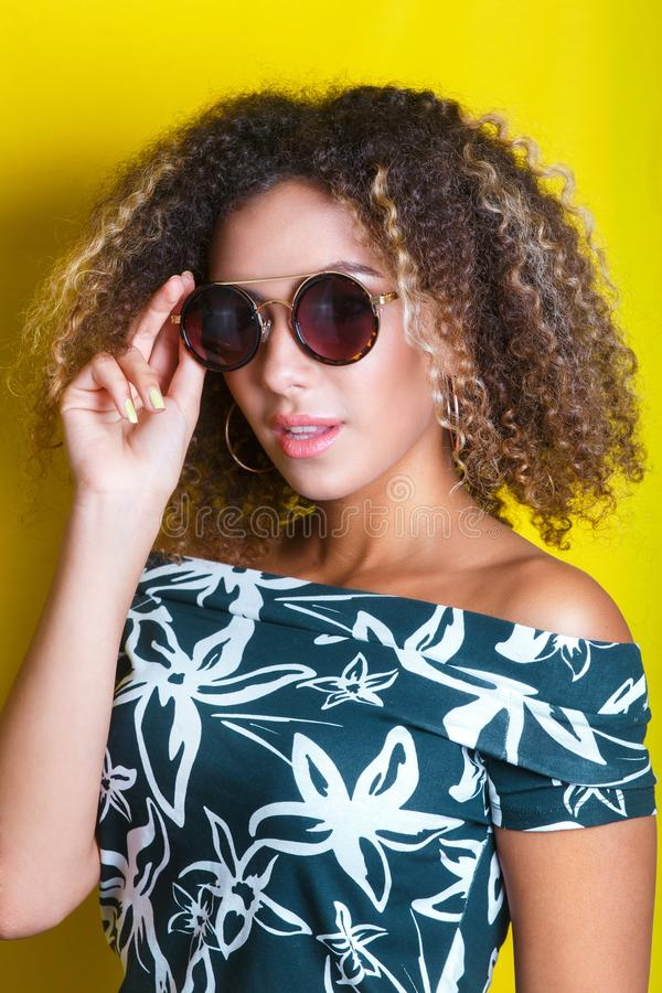Portrait of a young afro american woman in sunglasses. Yellow background. Lifestyle. Portrait indoors of a young afro american woman in sunglasses. Yellow stock photos