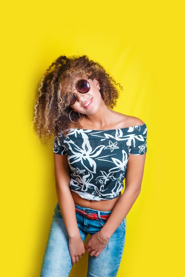 Portrait of a young afro american woman in sunglasses. Yellow background. Lifestyle. royalty free stock images