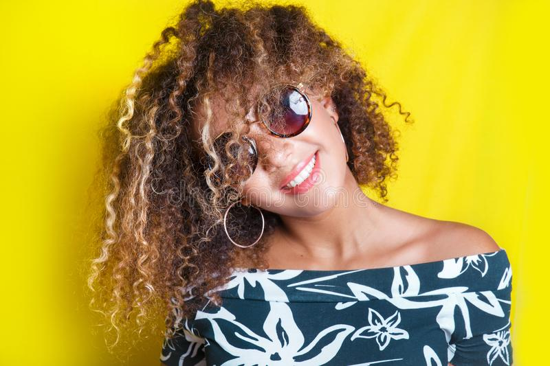 Portrait of a young afro american woman in sunglasses. Yellow background. Lifestyle. Portrait indoors of a young afro american woman in sunglasses. Yellow royalty free stock photography