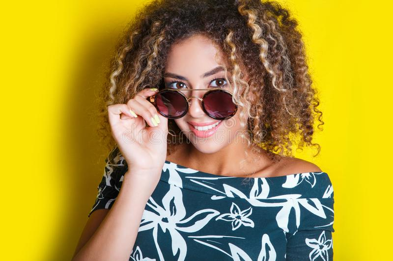 Portrait of a young afro american woman in sunglasses. Yellow background. Lifestyle. Portrait indoors of a young afro american woman in sunglasses. Yellow royalty free stock photos