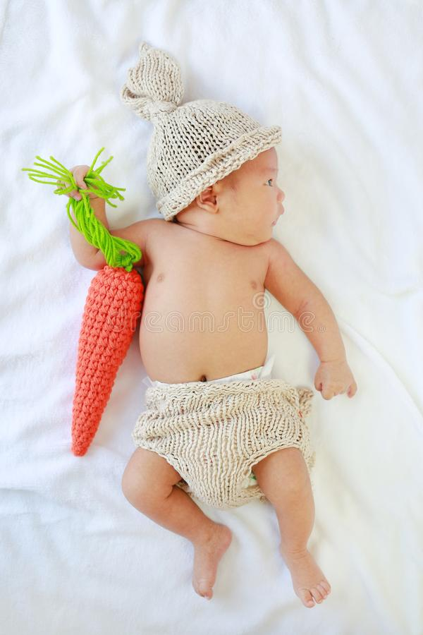 Portrait of infant baby boy lying on white background decorate with carrot Knitting. Top view royalty free stock photo