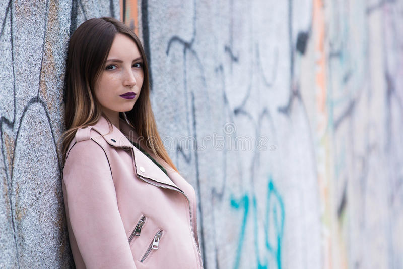 Portrait of informal fashionable girl on graffiti wall background. Portrait of beautiful informal fashionable girl on graffiti wall background stock photos