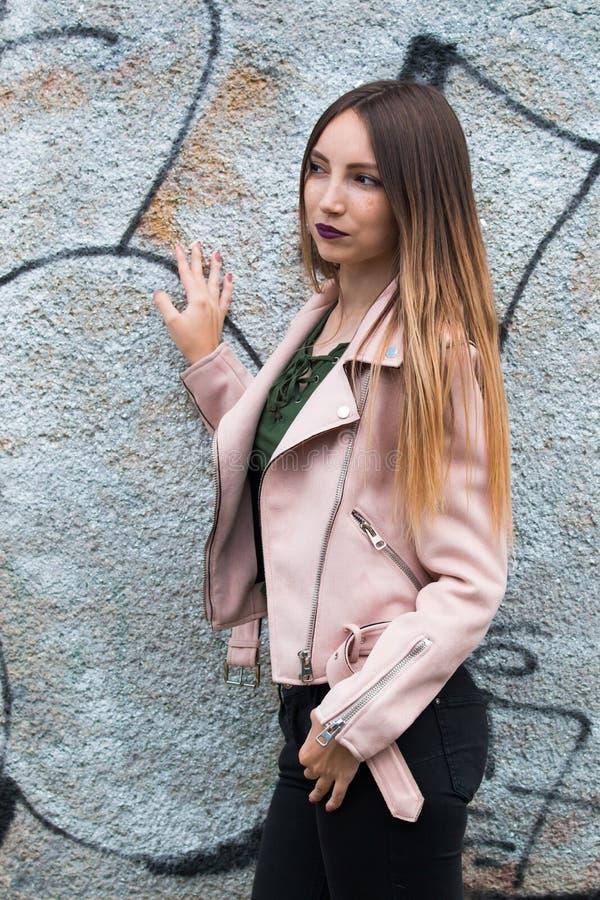 Portrait of informal fashionable girl on graffiti wall background. Portrait of beautiful informal fashionable girl on graffiti wall background stock photo