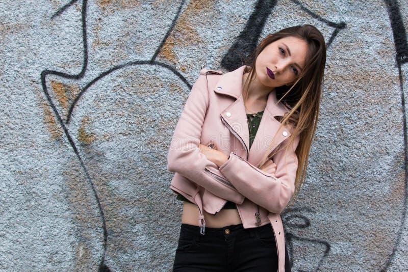 Portrait of informal fashionable girl on graffiti wall background. Portrait of beautiful informal fashionable girl on graffiti wall background royalty free stock image