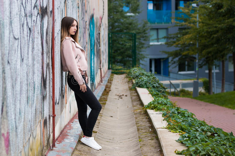 Portrait of informal fashionable girl on graffiti wall background. Portrait of beautiful informal fashionable girl on graffiti wall background stock images