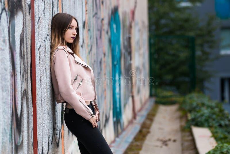 Portrait of informal fashionable girl on graffiti wall background. Portrait of beautiful informal fashionable girl on graffiti wall background royalty free stock photo