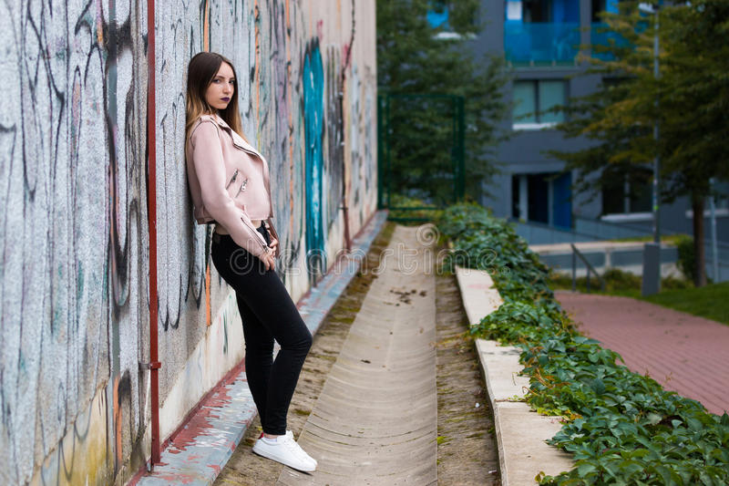 Portrait of informal fashionable girl on graffiti wall background. Portrait of beautiful informal fashionable girl on graffiti wall background royalty free stock images