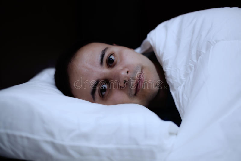Portrait of an insomniac man in his bed stock photography