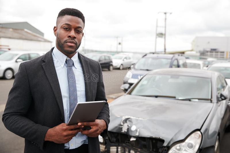 Portrait Of Insurance Loss Adjuster With Digital Tablet Inspecting Damage To Car From Motor Accident stock images