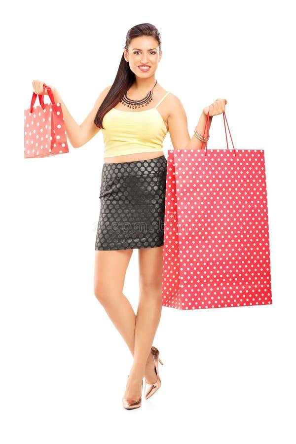 Portrait intégral d'un Ba se tenant femelle attrayant d'achats photo stock