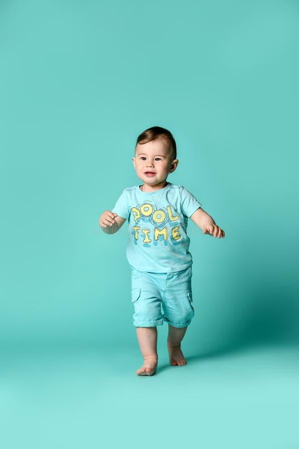 Portrait intégral d'un garçon d'enfant en bas âge dans un costume bleu de coton d'été d'isolement à un arrière-plan de turquoise photos stock