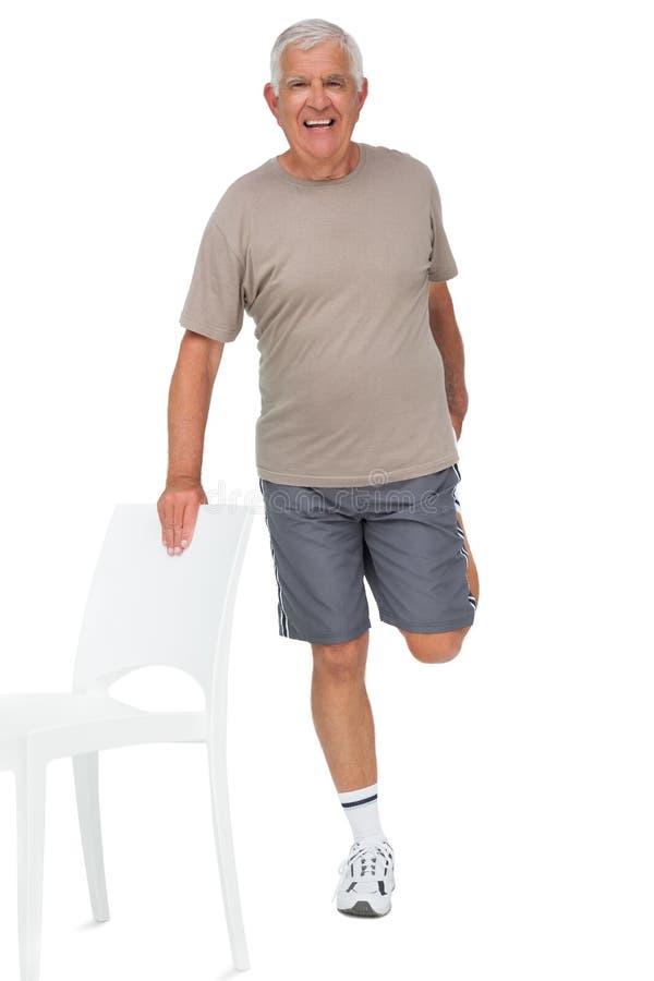 Portrait intégral d'un homme supérieur heureux étirant la jambe photo stock