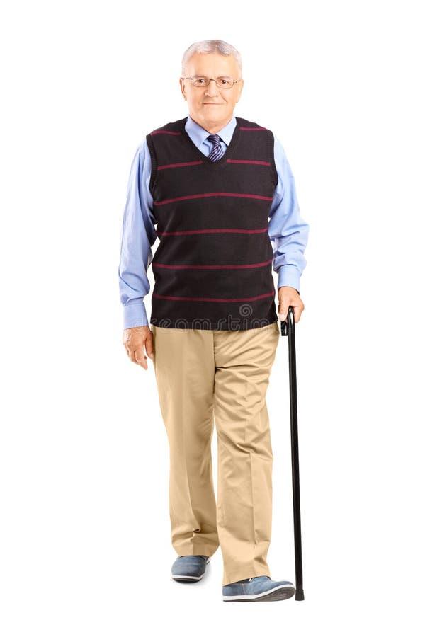 Portrait intégral d'un homme supérieur marchant avec une canne photo libre de droits