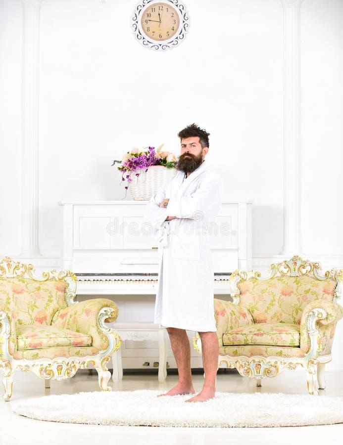 Portrait intégral d'un jeune homme dans une robe longue d'isolement dans la chambre blanche Type barbu brutal se tenant avec ses  image stock