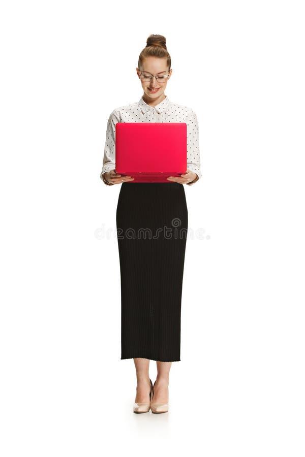 Portrait intégral d'un professeur féminin de sourire jugeant un ordinateur portable d'isolement sur le fond blanc photos stock