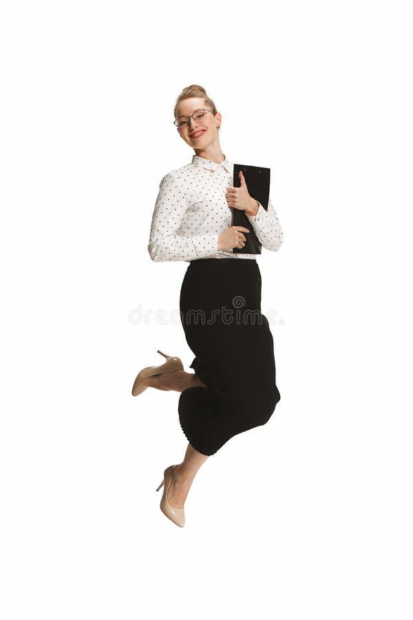 Portrait intégral d'un professeur féminin de sourire tenant un dossier sautant sur le fond blanc image stock