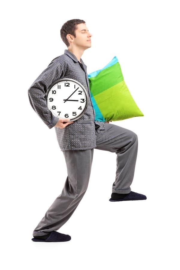 Portrait intégral d'un somnambule avec un oreiller et une horloge photos libres de droits