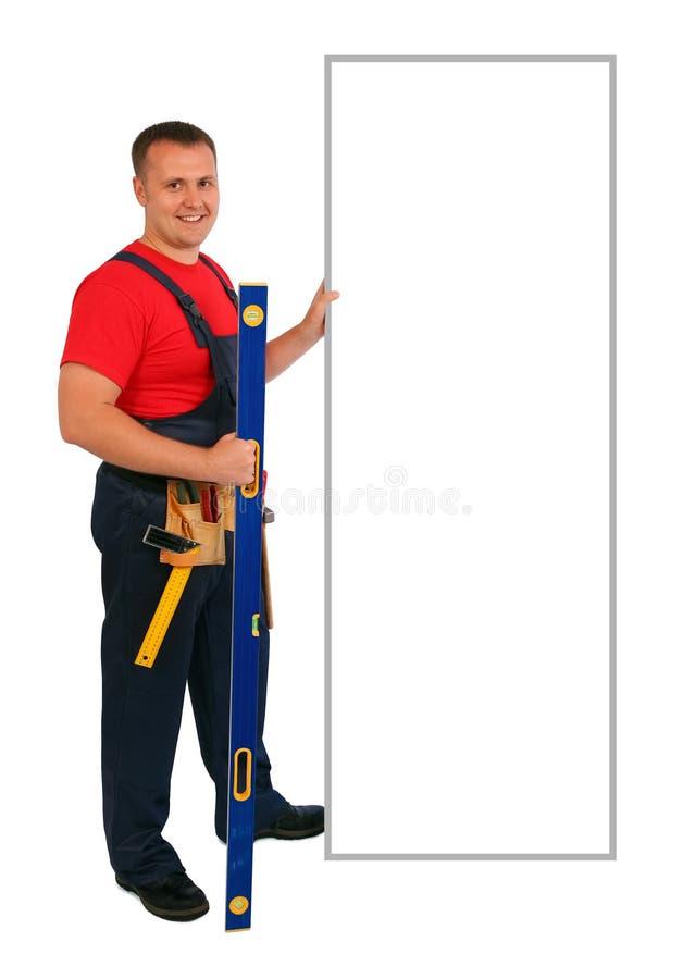 Portrait intégral d'un travailleur de la construction caucasien heureux dirigeant quelque chose sur un panneau d'affichage vide D photos stock